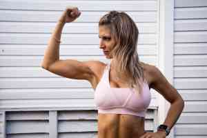 a strong female flexes her muscles while wearing a sports bra