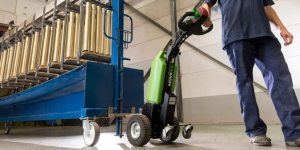 Movexx walk-behind tugger being used in an industrial application typically handled by manually-moved carts.
