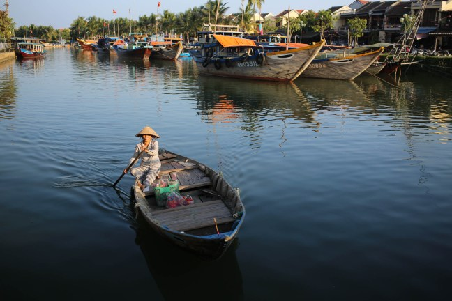 Lady steering a boat in Hoi An