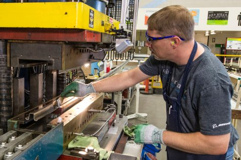 Auburn, Wash., Oct. 13, 2014 – Boeing (NYSE: BA) has started production of the first 737 MAX fuselage stringers at Boeing Fabrication Integrated AeroStructures in Auburn, Wash. Stringers run the length of the fuselage structure giving it stability and strength. Pictured here, Joggle Press operator Rich Harrison prepares the first 737 MAX fuselage stringer for the press by brushing on lubricant. The press applies up to 100 tons (90,718 km) of pressure to form small jogs in the metal to engineering design specifications./Boeing