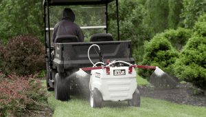 A professional applicator spraying a large lawn.