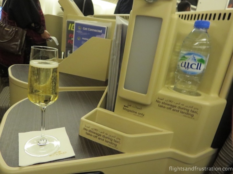 Complimentary water at the seat and enjoying champagne on Etihad Airways