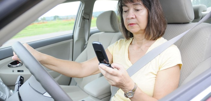 Woman driver distracted by looking at cell phone