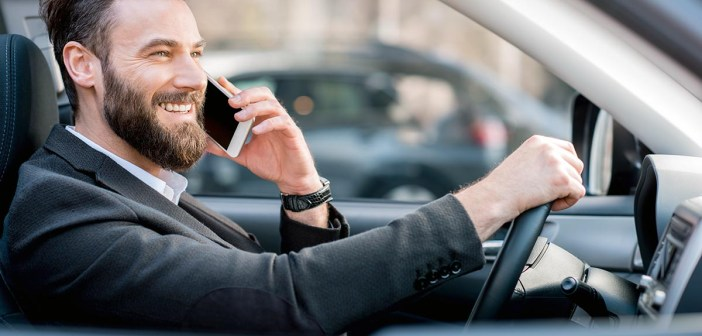 Handsome businessman talking with phone while driving a car in the city