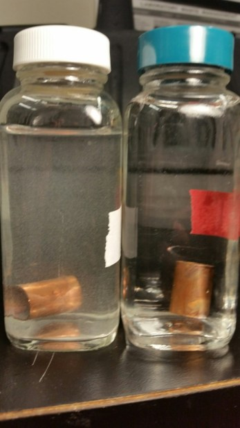 Figure 1: Samples of lead solder connected to copper pipe in Flint River water with orthophosphate (left) and Detroit water (right). The white suspended particles visible in the Flint River water are tiny lead particles while the Detroit water remained clear