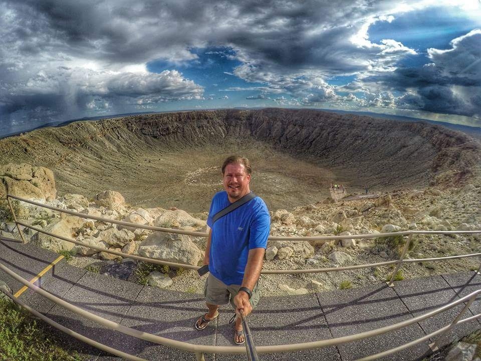Greg Berndt from Flip Flop Wanderer standing in front of the Meteor Crater in Arizona. This image is on his About Page.