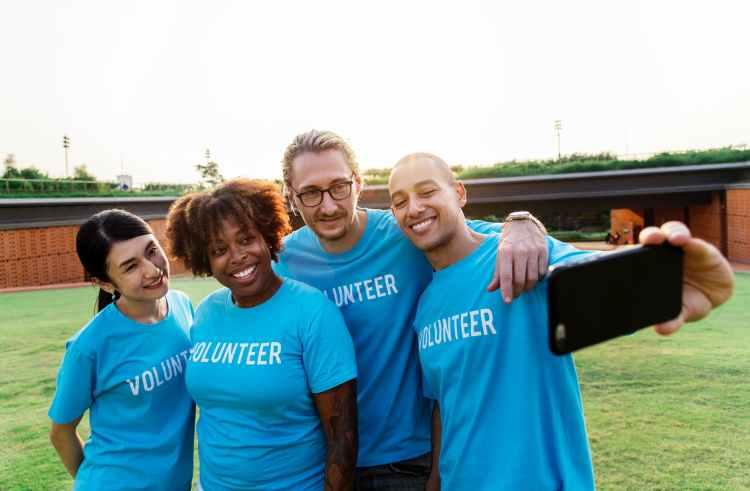 four person taking selfie while wearing blue volunteer t shirt