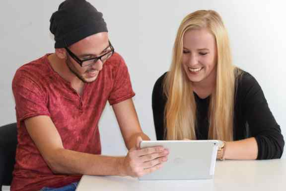 2 Schüler um ein Tablet