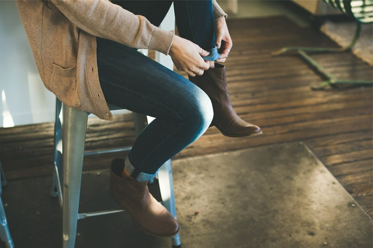 a woman wearing boots, jeans, and a cardigan