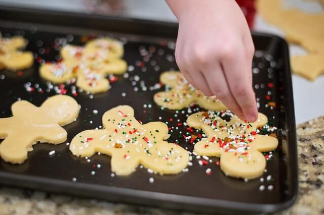 Kid putting sprinkles on cookies before baking