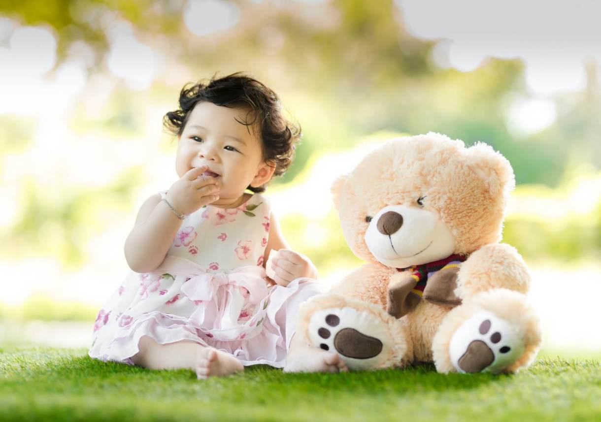 Baby girl sitting on a green grass beside a bear plush toy