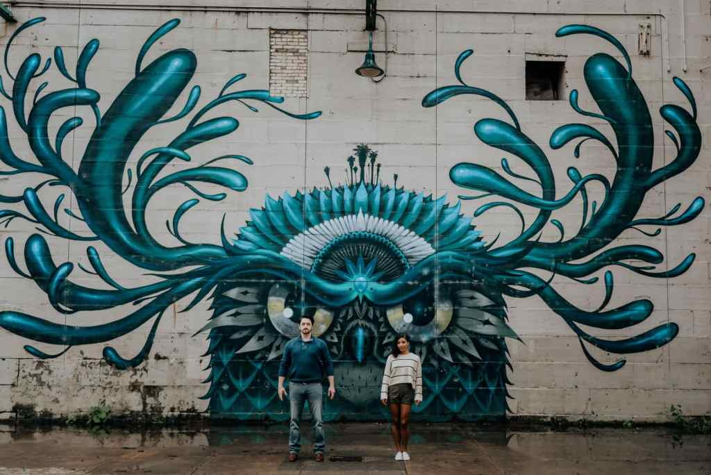 A couple stands in front of a mural of an owl-like creature