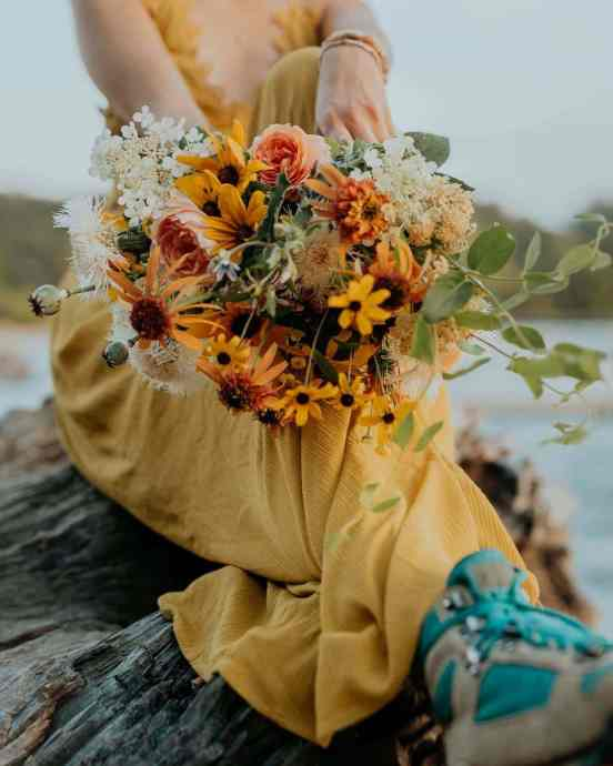 A bride in a yellow dress and vintage hiking boots shows off her bouquet.