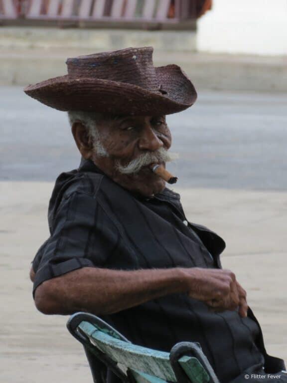 Old man smoking Cuban cigar on bench Cienfuegos