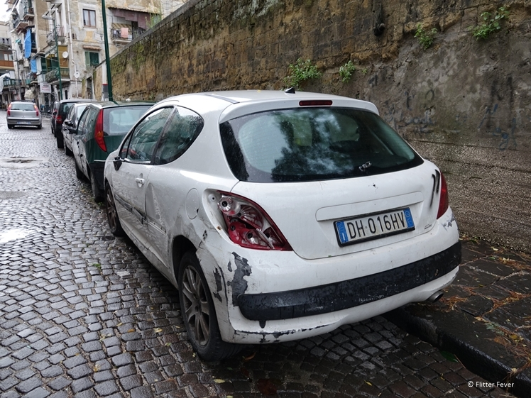 Damaged car in streets of Naples - typical