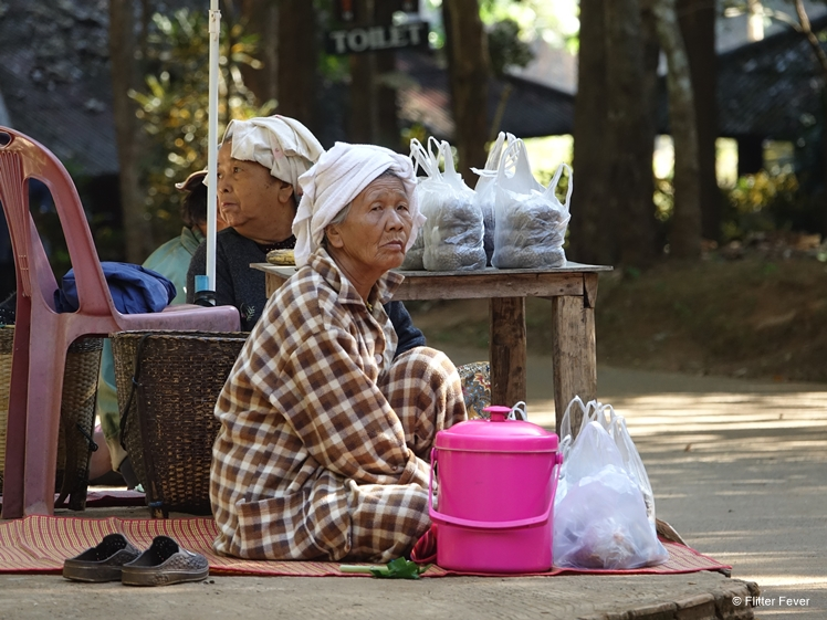 Local woman selling fish food at the entrance of Lod Cave