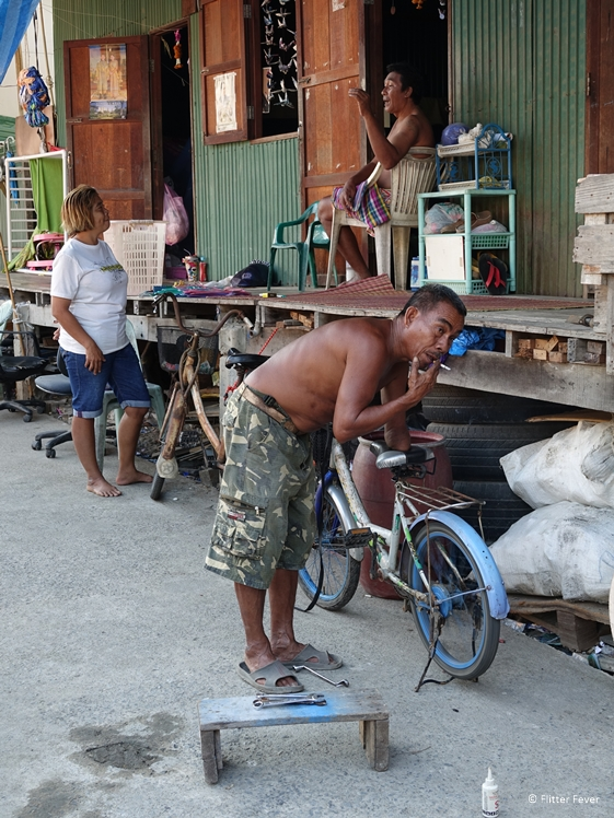Father fixing bicycle and man and woman talking on background in slum of Bangkok