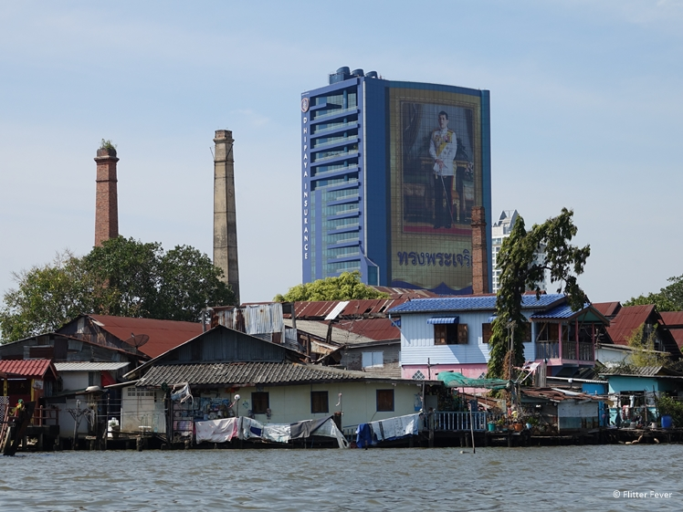 Slum houses seen from the Chao Phraya River, Bangkok with photo of Thai King on business building at the background