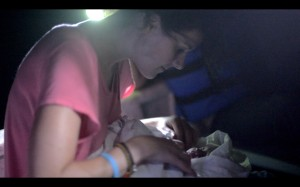 Dr. Kim checking on the newborn during the boat ride.