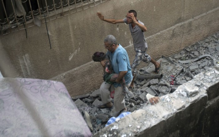 導彈攻擊後,一位男士抱著小孩的屍體離開現場。