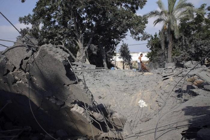 一位巴勒斯坦男子在破爛的房屋裡找還可以用的物資。