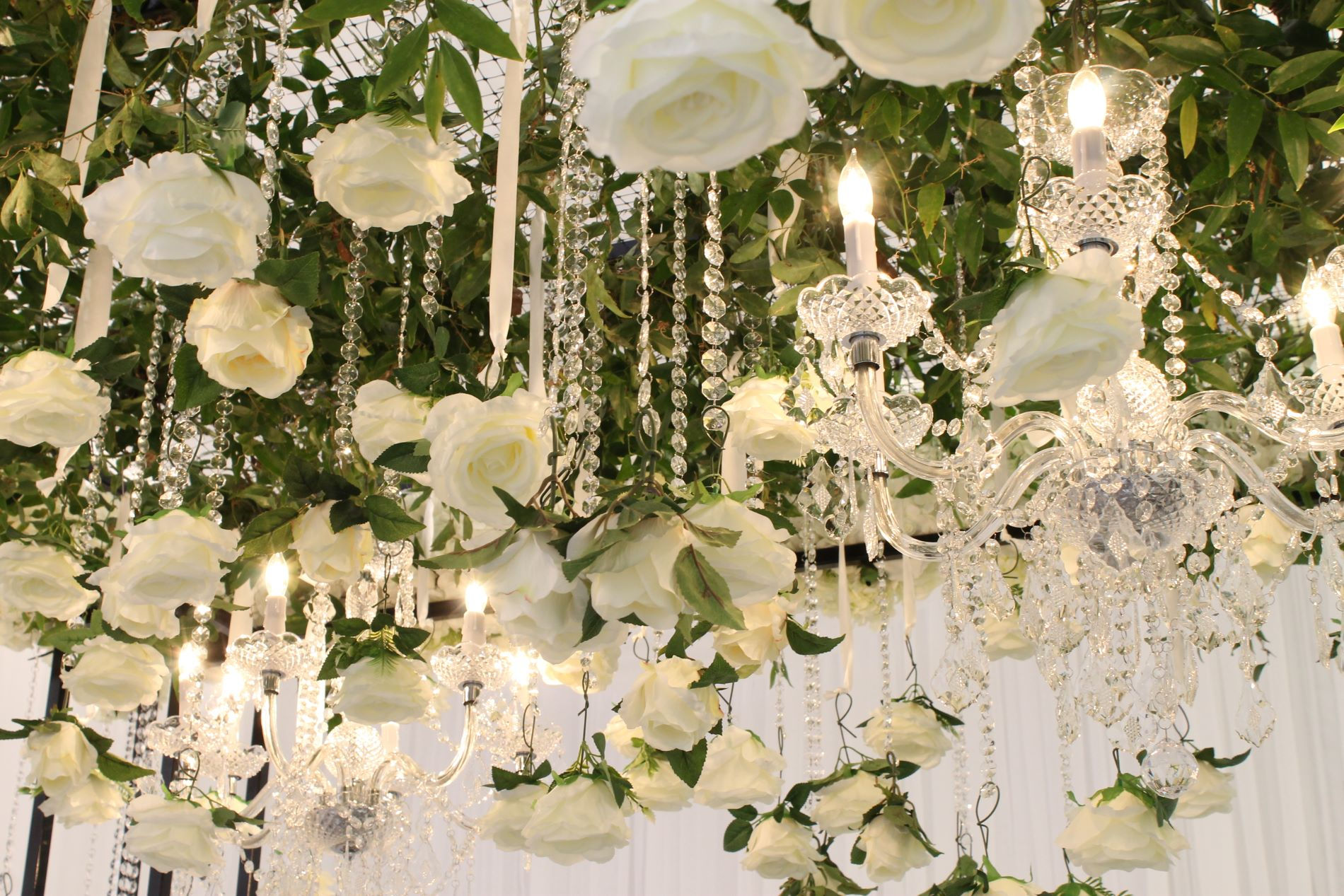 greenery, crystals and white roses hanging from wedding arch