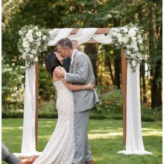 Symmetrical floral on wood arbor with ivory chiffon