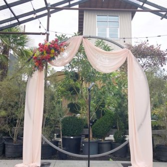 Circular arbor with blush drape and asymmetrical floral accent at Blockhouse