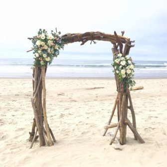 Driftwood arbor with 2 asymmetrical floral accents on the beach
