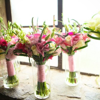 fun pink bridesmaids bouquets and an elegant white calla lily bouquet