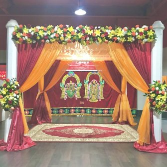 traditional style mandap with orange & red drapes