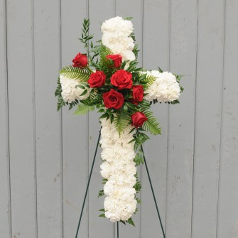 White carnation cross with red roses accent