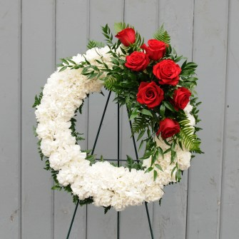 White carnation wreath with red rose accent