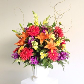 Vibrant life floral arrangement in an urn