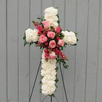 White carnation cross with pink floral accent