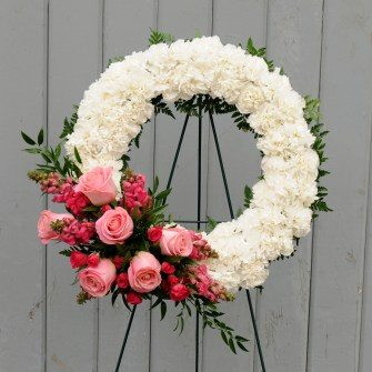 White carnation wreath with pink floral accent