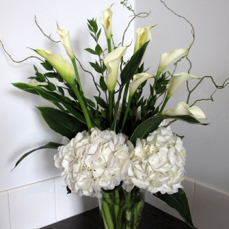 Arrangement of white calla lilies and white hydrangeas, stylized with curly willow