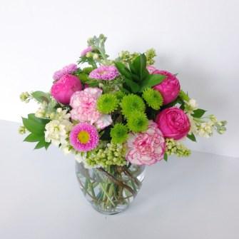 medium springy colorful arrangement of flowers, including garden roses