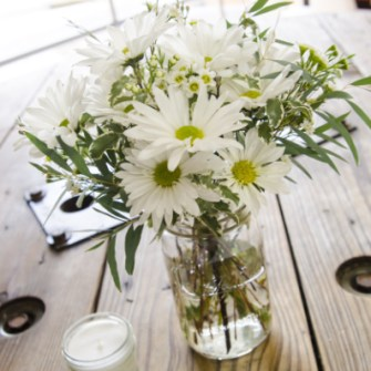 daisies and greens in a mason jar