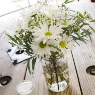daisies and greens in a mason jar