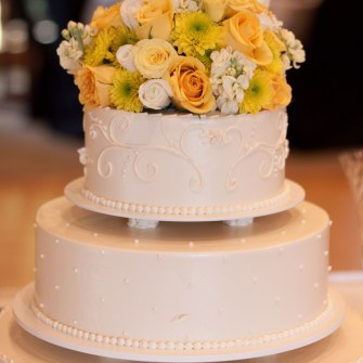 mixed yellow and white flowers a on multi-layered cake