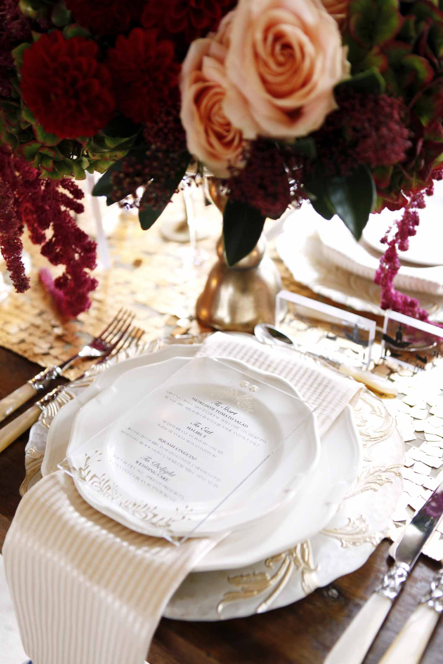 Place setting of gold rimmed plates, striped gold napkin, lucite menu card, and lush flowers for style shoot at Kloster Eberbach by Flora Nova Design Seattle