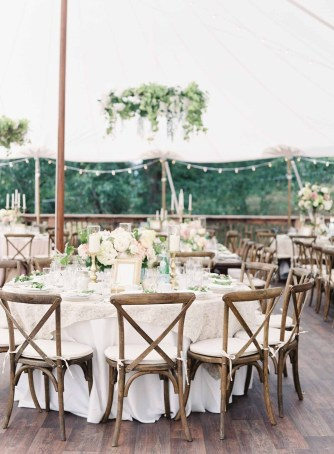 Tent wedding reception with ceiling greenery wreaths, tables with ivory linens, Vineyard chairs and garden flower centerpieces - designed by Flora Nova Design Seattle