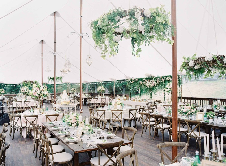 Grand Seattle tent wedding with long wooden farm tables and vineyard chairs, greenery wreaths in the ceiling, and blush centerpieces - Seattle Wedding designed by Flora Nova Design