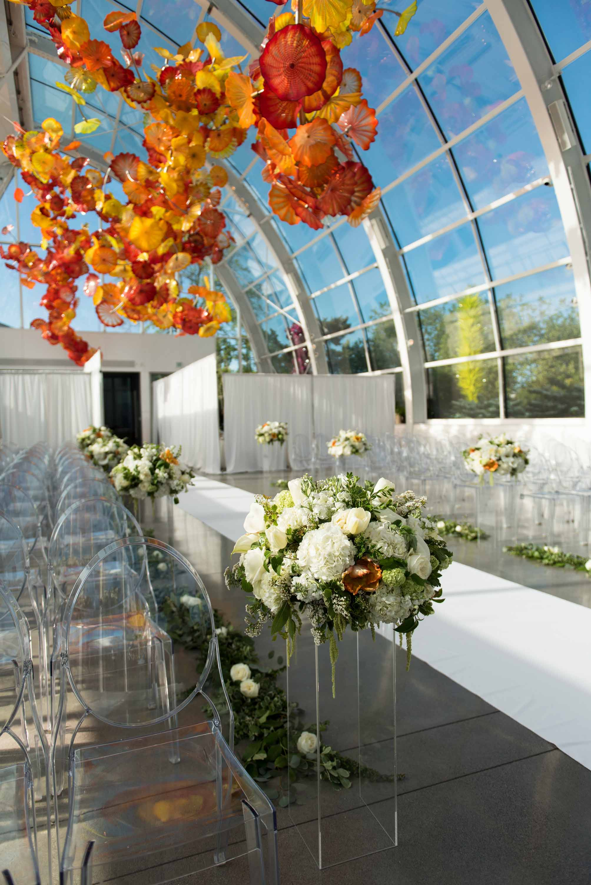 Wedding ceremony aisle at Chihuly Garden and Glass wedding with large white flower arrangements decorating the aisle - designed by Flora Nova Design