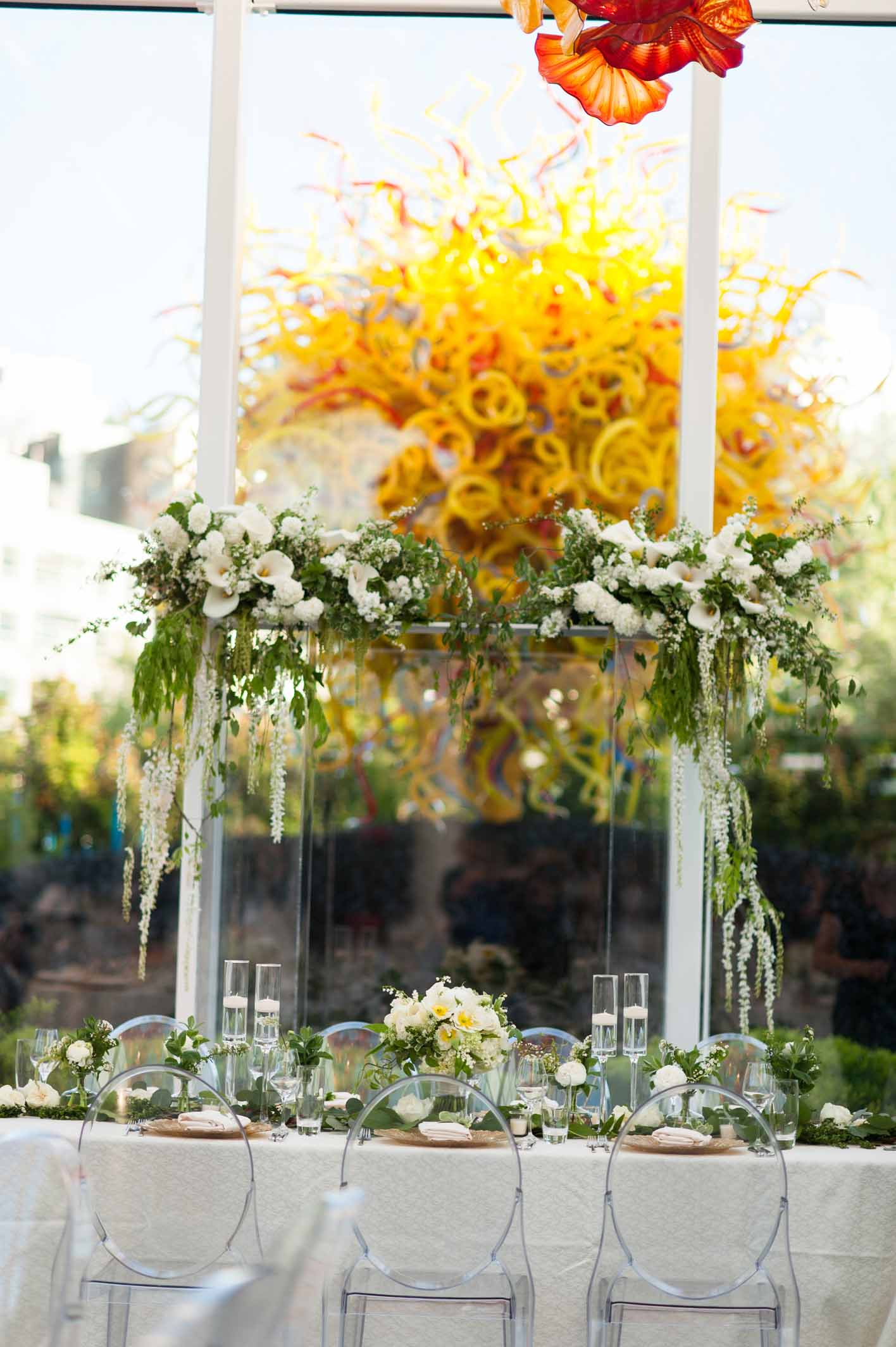 Head table at Chihuly Garden and Glass wedding with large clear lucite arbor covered in greenery and white flowers