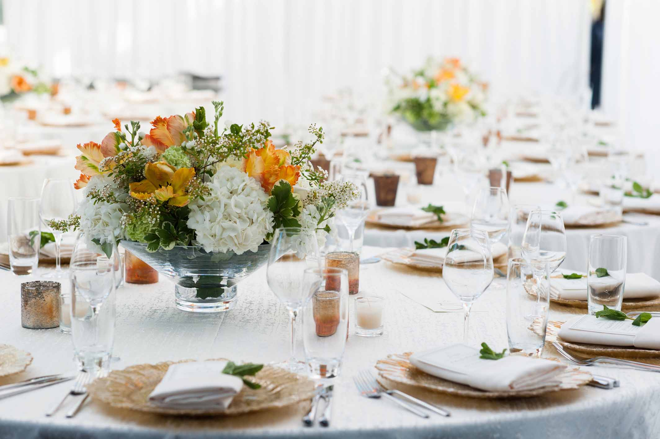 Wedding reception table with centerpieces of white and orange spring flowers on round table with gold charger plates, gold votive candles