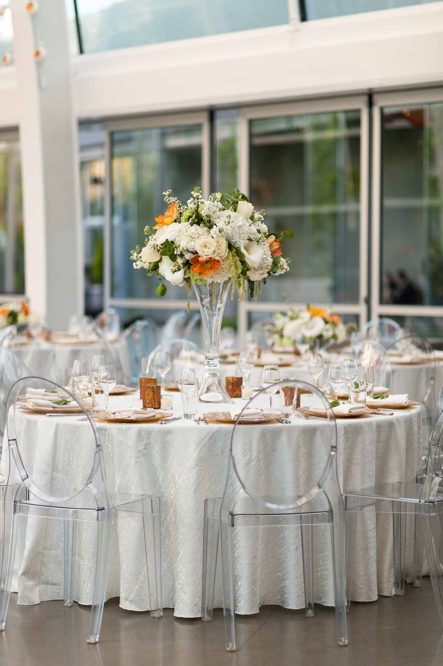 Wedding reception table with white linen, clear lucite chairs, tall centerpiece with orange and white flowers on tall crystal vase