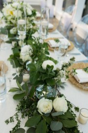 Head table lined with greenery and white flowers