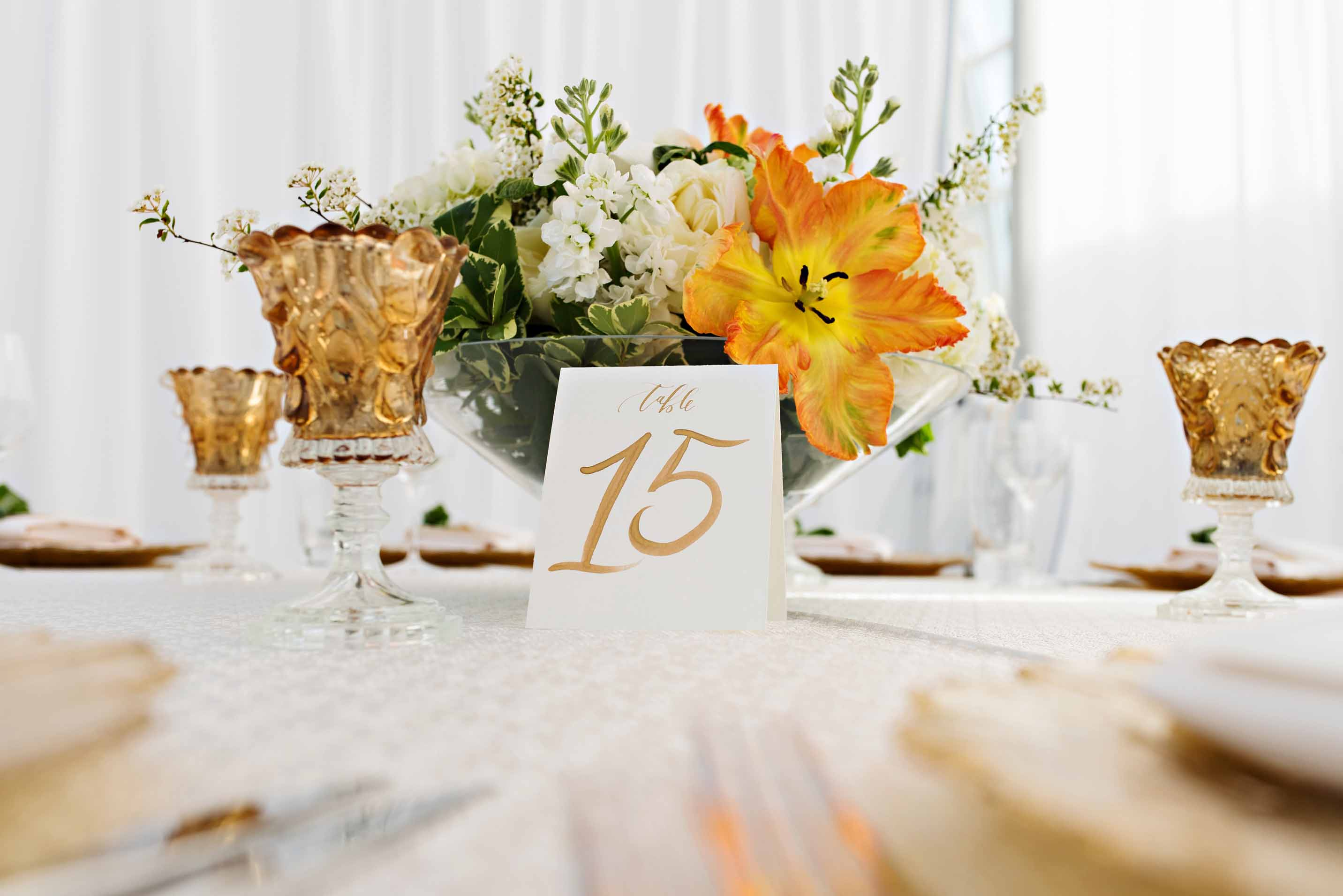 Low centerpiece with large orange parrot tulips, and a gold votive candle holder